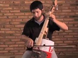 a cello made from an oil can and landfill trash